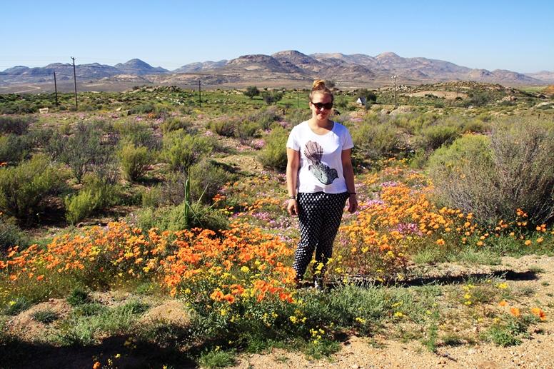 Lynn steht mitten in dem Blütenmeer im Namaqualand