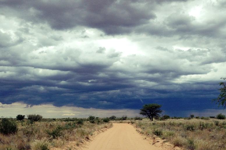 Regenwolken über einer einsamen Straße in der Kalahari in Namibia