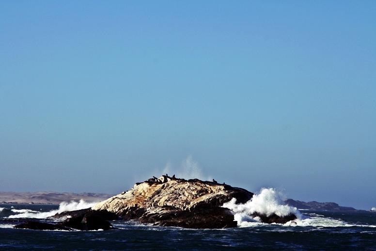 Ein Felsen mit Seelöwen im stürmenden Atlantik bei Lüderitz in Namibia