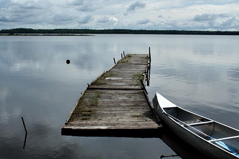 Spiegelglatter See mit Steg und Kanu