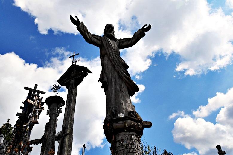 Ein hölzener Jesus breitet seine Arme aus auf dem Berg der Kreuze eine der Sehenswürdigkeit in Litauen