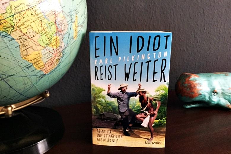Buch ein Idiot reist weiter präsentiert. Im Hintergrund eine schwarze Wand und ein Globus.