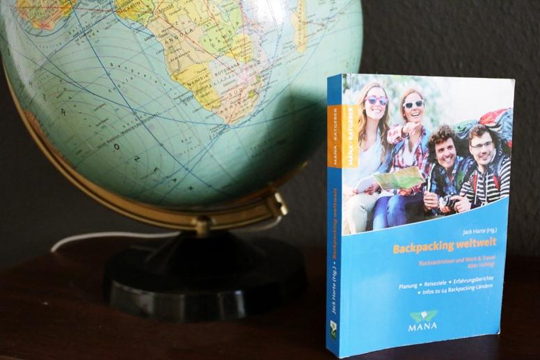 Das Cover des Buches Backpacking weltweit mit Globus um Hintergrund