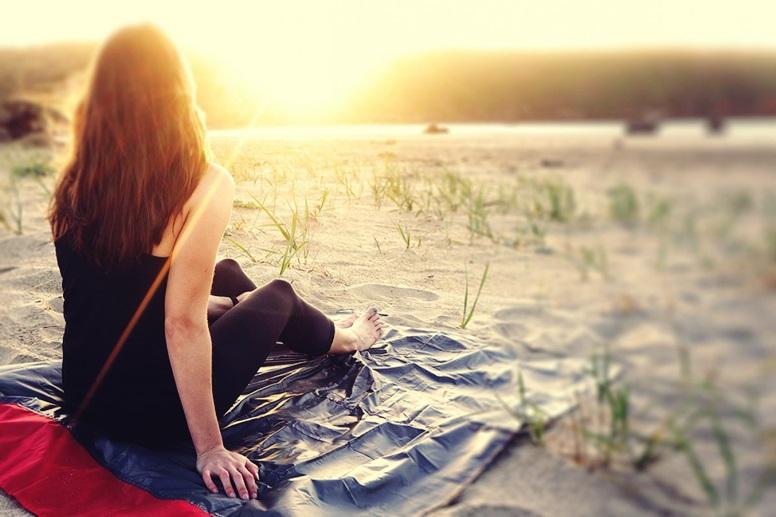 Frau auf Taschendecke am Strand als Idee für Weihnachtsgeschenke für Weltenbummler