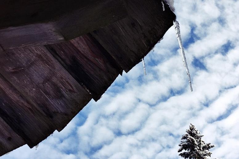 Blick in den Himmel mit Dach und herunterhängenden Eiszapfen