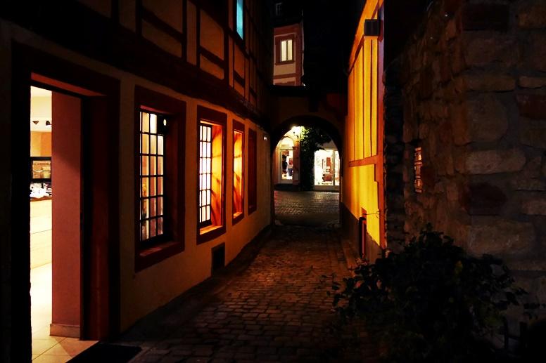 Licht fällt durch die Fenster auf eine dunkle Gasse in der Mainzer Altstadt