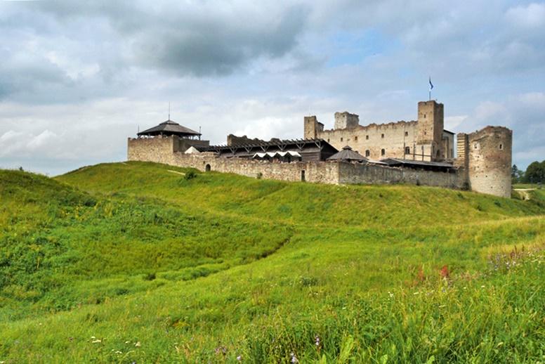 Blick über grüne Hügel auf die Burg Rakvere in Estland