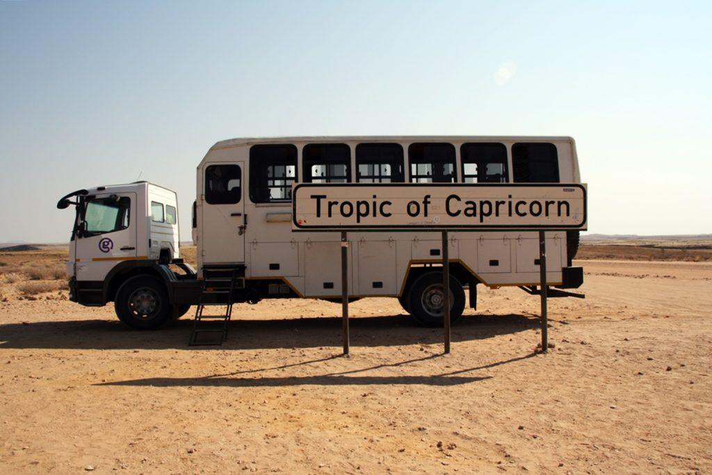 Truck hinter dem Tropic of Capricorn Schild in Namibia
