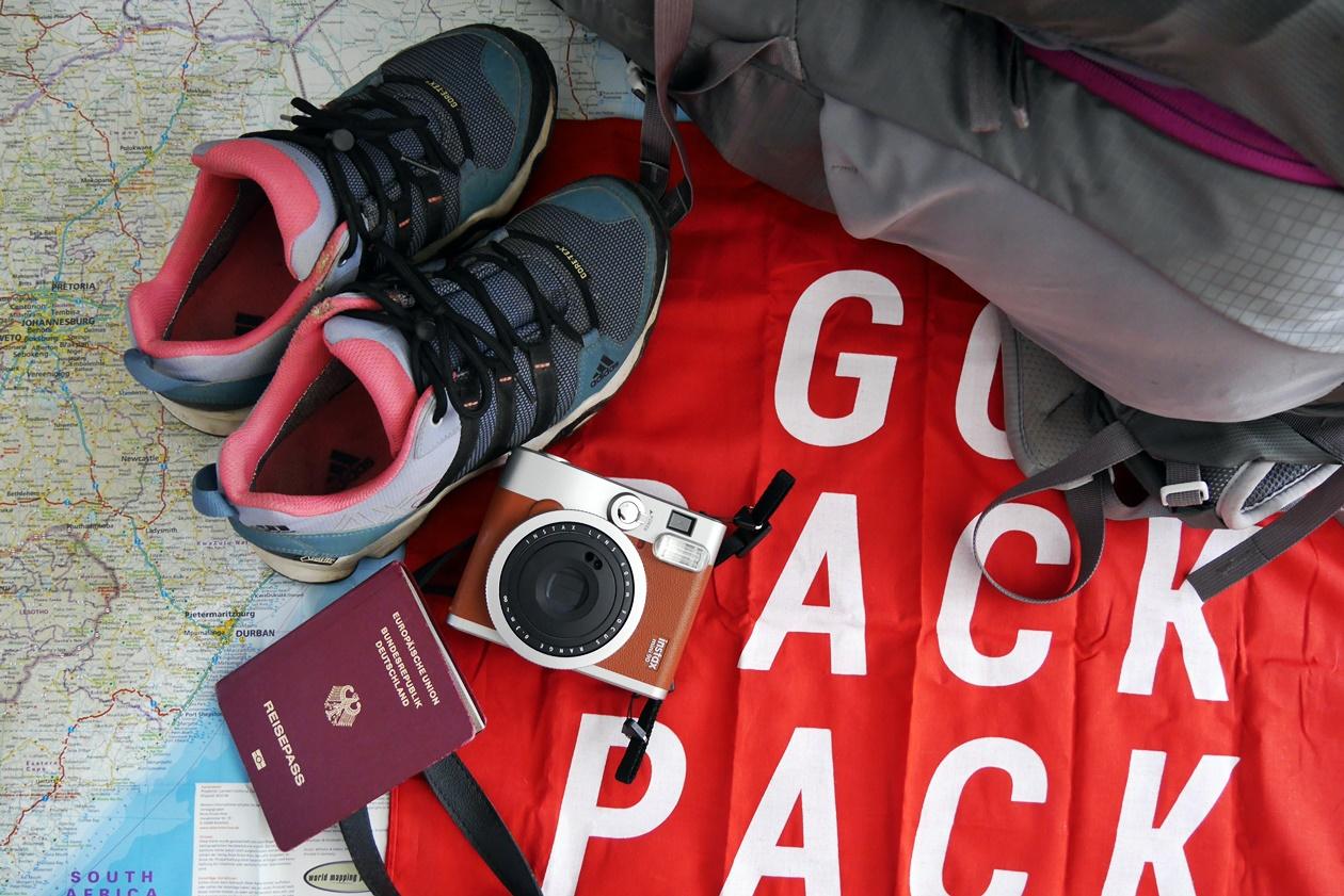 Schuhe, Rucksack und Reisepass, die zur Packliste Südafrika gehören