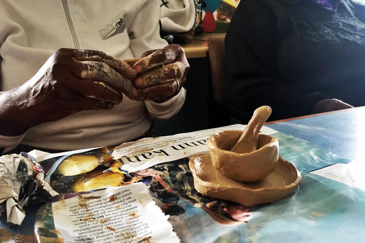 Hände einer Frau, die mit Lehm gearbeitet hat
