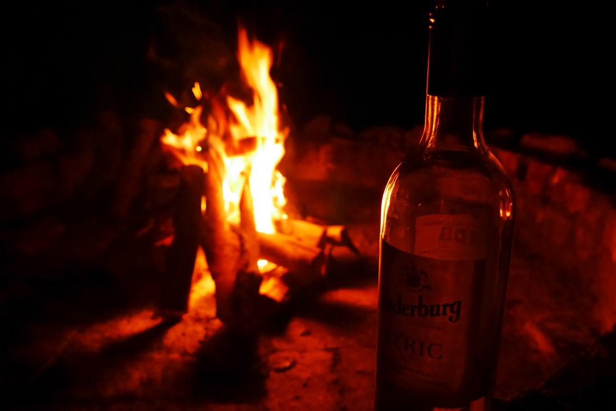 Lagerfeuer mit Wein im Bush Camp von !Khwa ttu auf unserem Wochenendausflug von Kapstadt