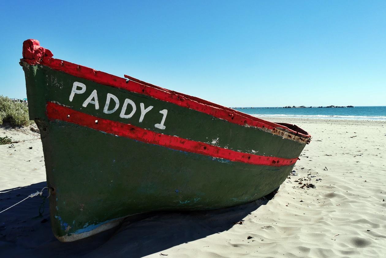 Grünes Fischerboot am Strand von Paternoster auf unserem Wochenendausflug von Kapstadt