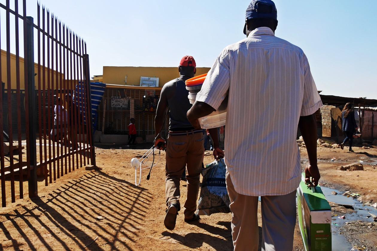Männer tragen Fernseher und Antenne nach Hause in Soweto. Aufgenommen auf einer Fahrradtour mit Lebo´s Backpackers