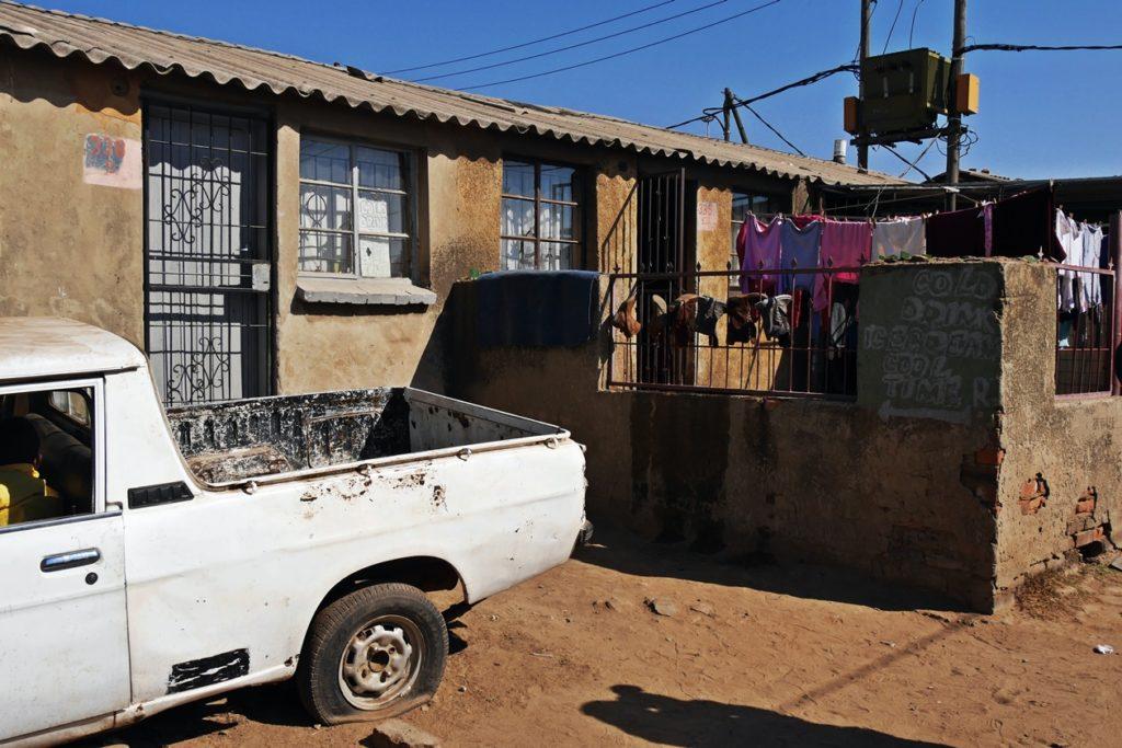 Auto mit kaputtem Reifen vor einem Wohnhaus in Soweto aufgenommen auf einer Fahrradtour durch Soweto mit Lebo´s Backpackers