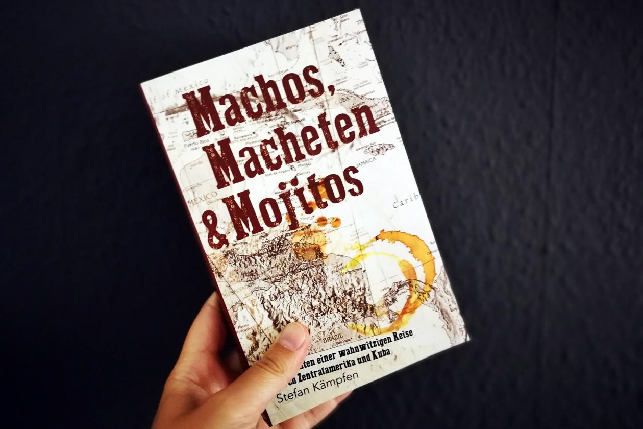 Hand mit dem Buch Machos, Macheten & Mojitos