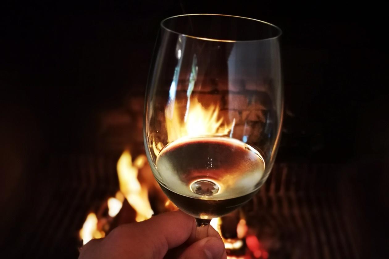 Glas Weißwein beim Winetasting vor einem Kaminfeuer in der Nähe von Kapstadt