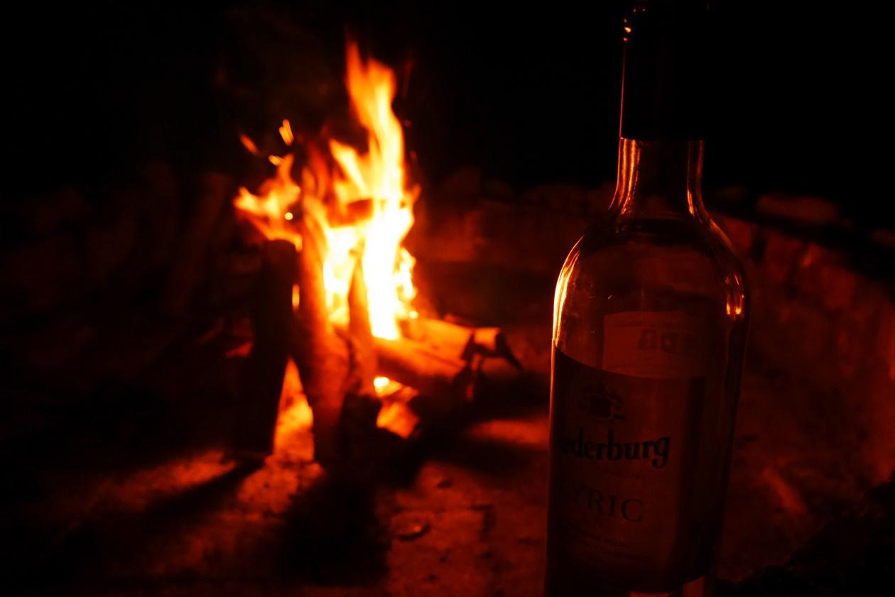 Lagerfeuer mit einer Flasche Wein an der Westküste von Südafrika