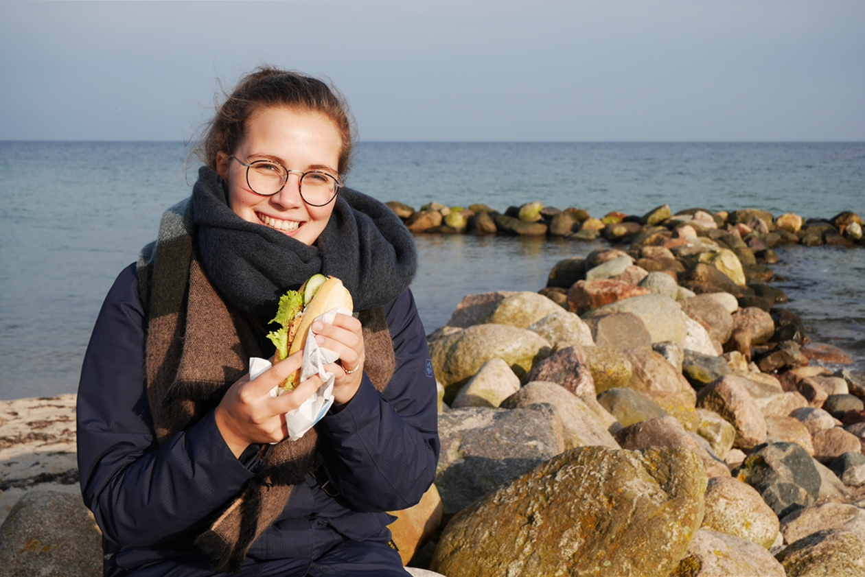 Lynn isst ein Fischbrötchen am Ostseestrand