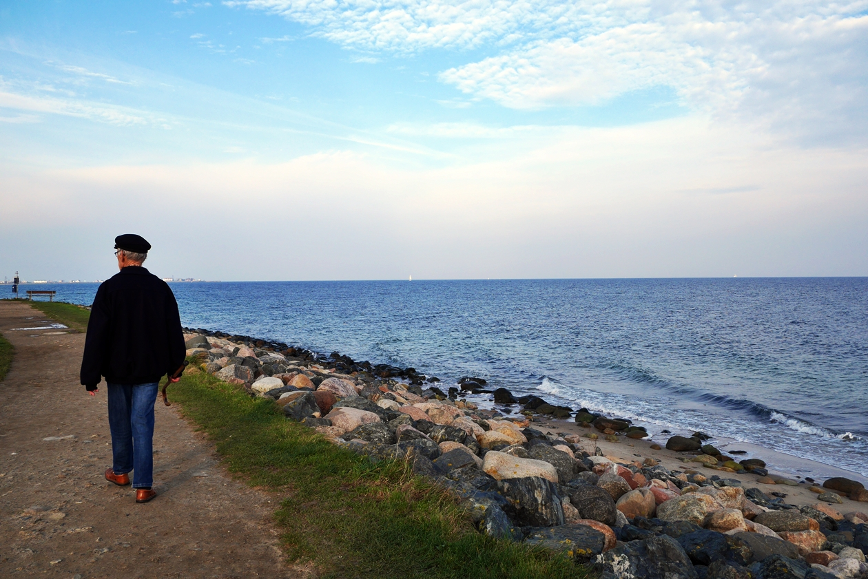 Mann spaziert am Ostseestrand von Schleswig-Holstein