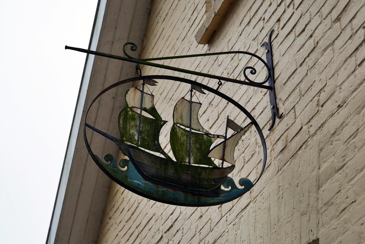 Schild mit Schiff, welches an einer Häuserwand hängt