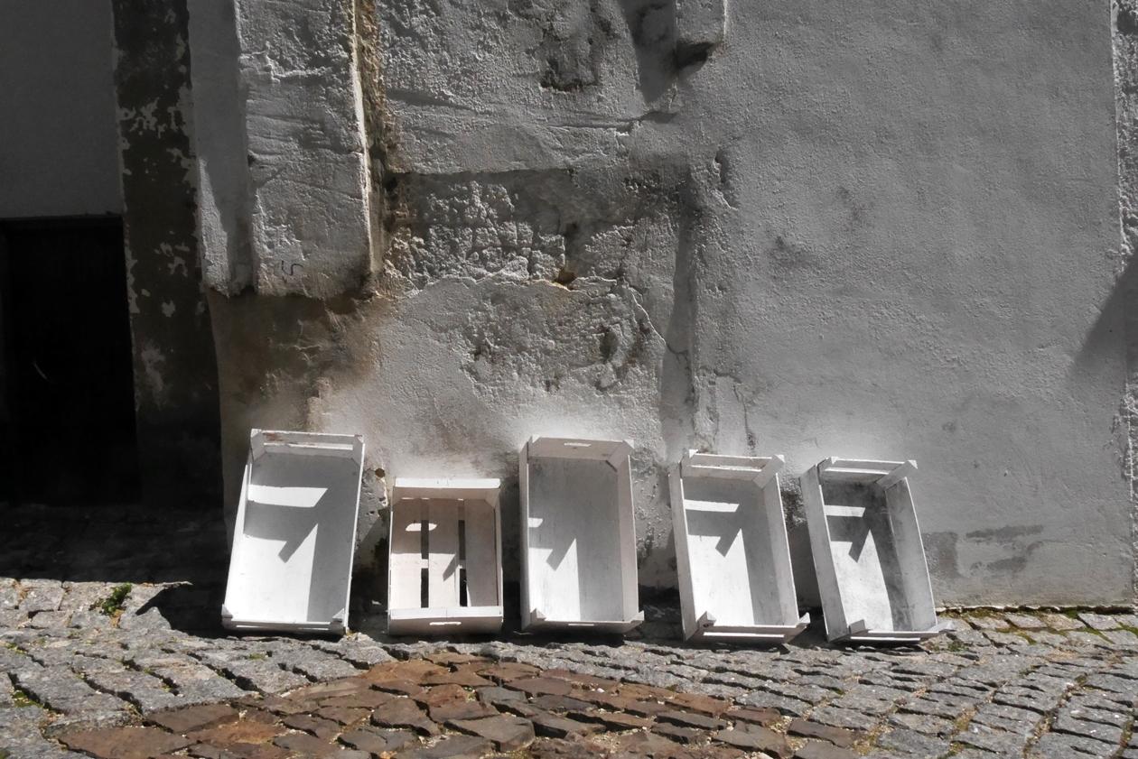 Kisten an einer Häuserwand in Aljezur