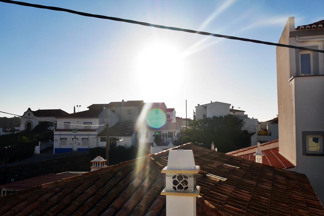 Blick auf die untergehende Sonne über den Häusern von Carrapateira