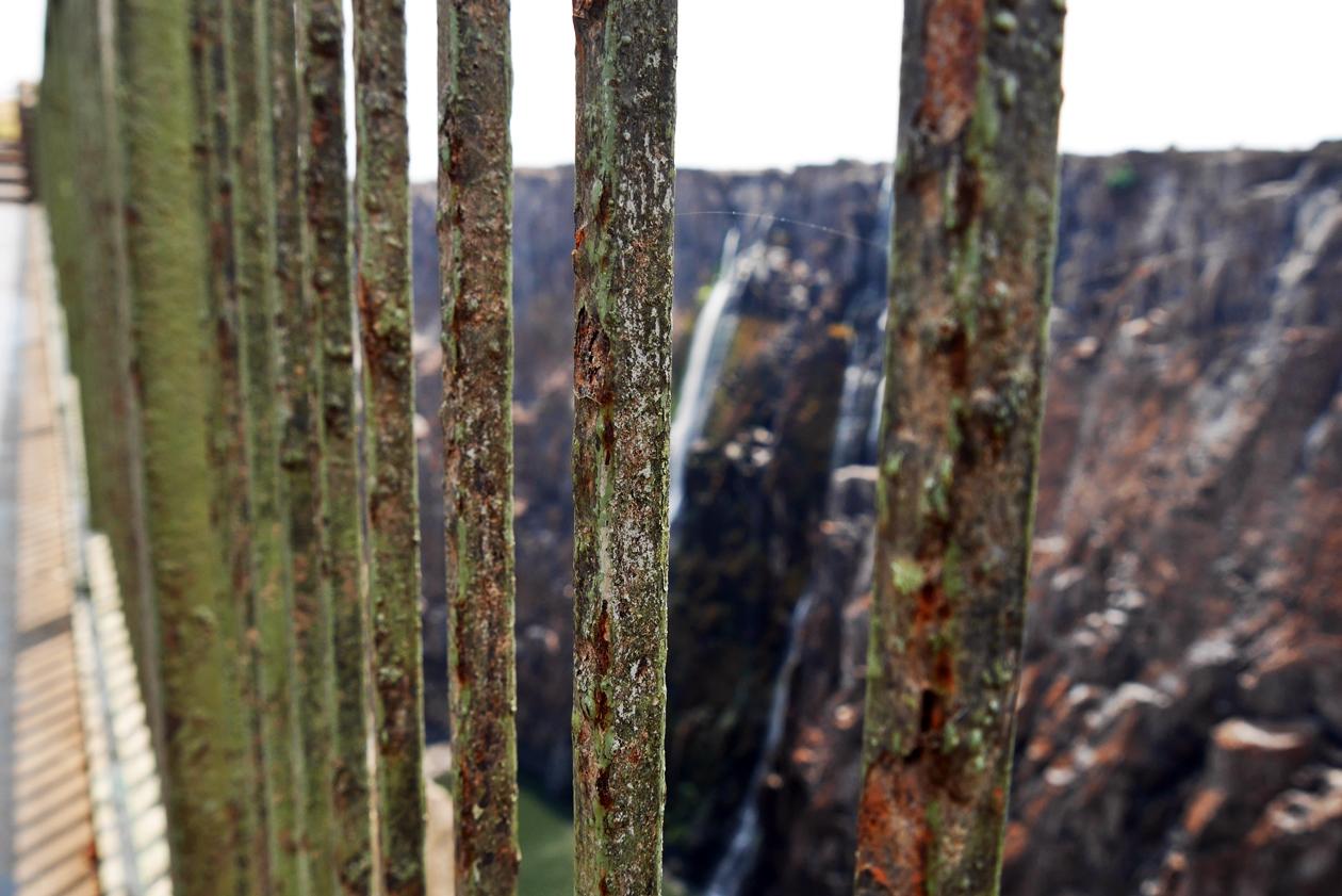 Blick durch die Gitterstäbe einer Brücke bei den Victoria Fällen