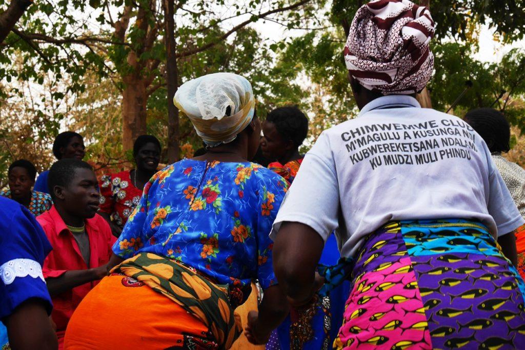 Frauen in bunten Röcken tanzen und singen zur Begrüßung im Chingalire Rural Homestay