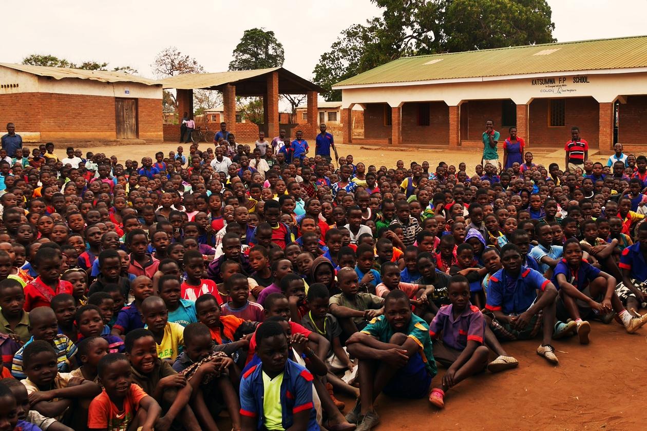 An die dreihundert Schüler*innen auf dem Schulhof einer lokalen Schule in Malawi