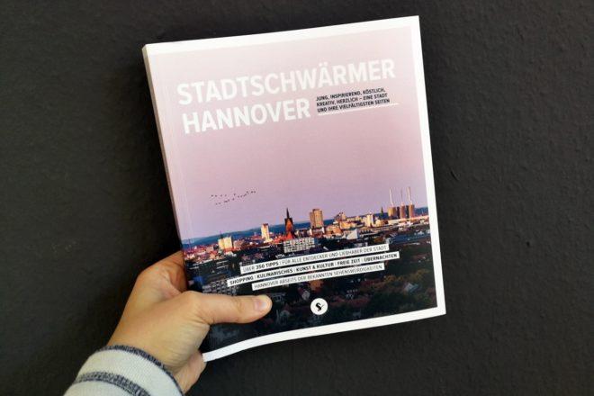 Hand mit dem Buch Stadtschwärmer Hannover