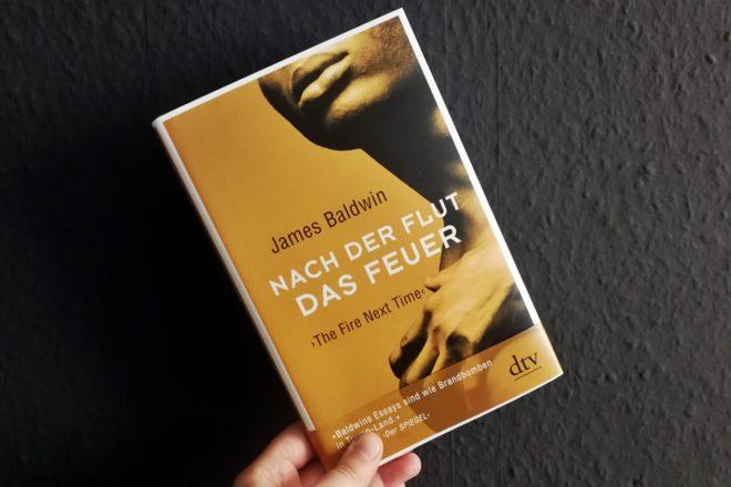 Hand mit dem Buch Nach der Flut das Feuer von James Baldwin