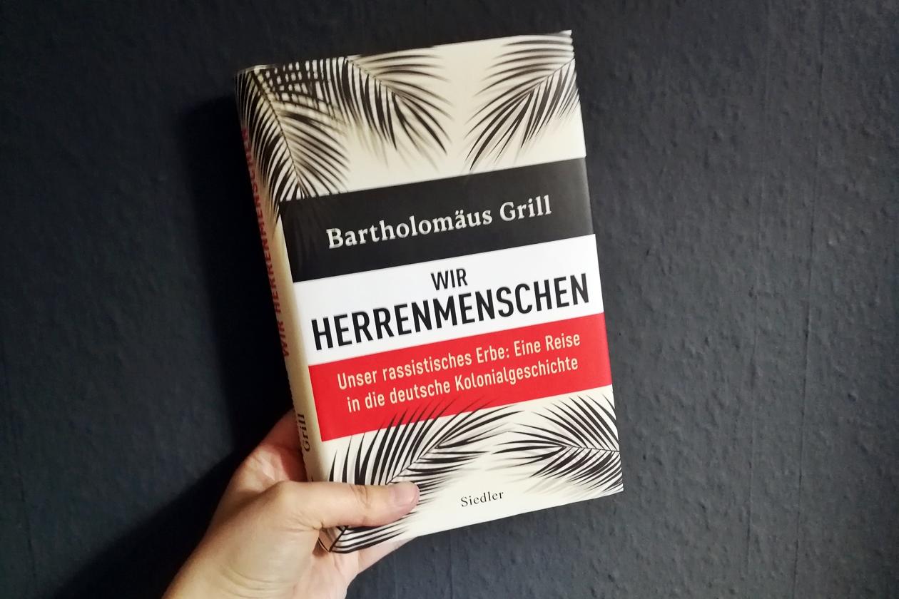 """Hand die das Buch """"Wir Herrenmenschen"""" von Bartholomäus Grill hält"""