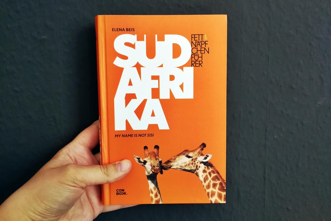 Hand mit dem Cover des Buches Fettnäpfchenführer Südafrika
