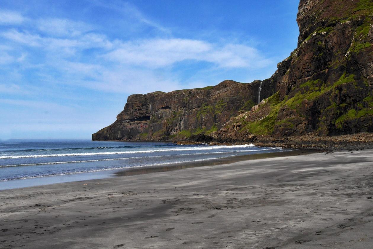 Der schwarze Sand der Talisker Bay mit einem Wasserfall im Hintergrund