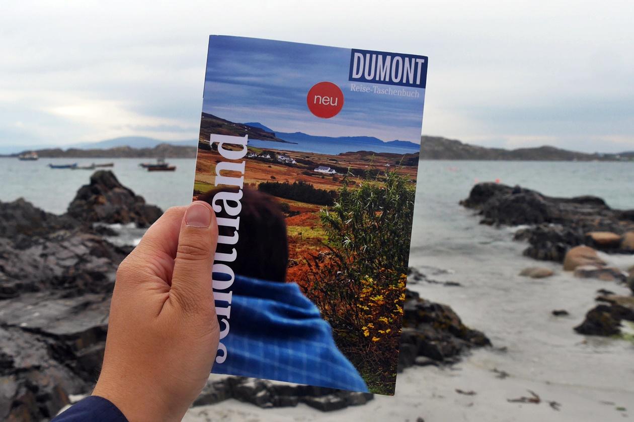 Hand die den Schottland Reiseführer von DuMont in der Hand hält