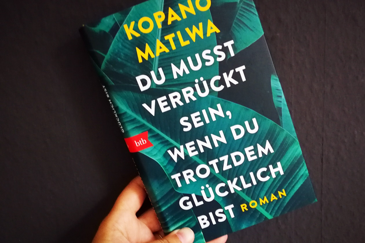 Hand die das Buch Du muss verrückt sein, wenn du trotzdem glücklich bist von Kopano Matlwa in den Händen hält