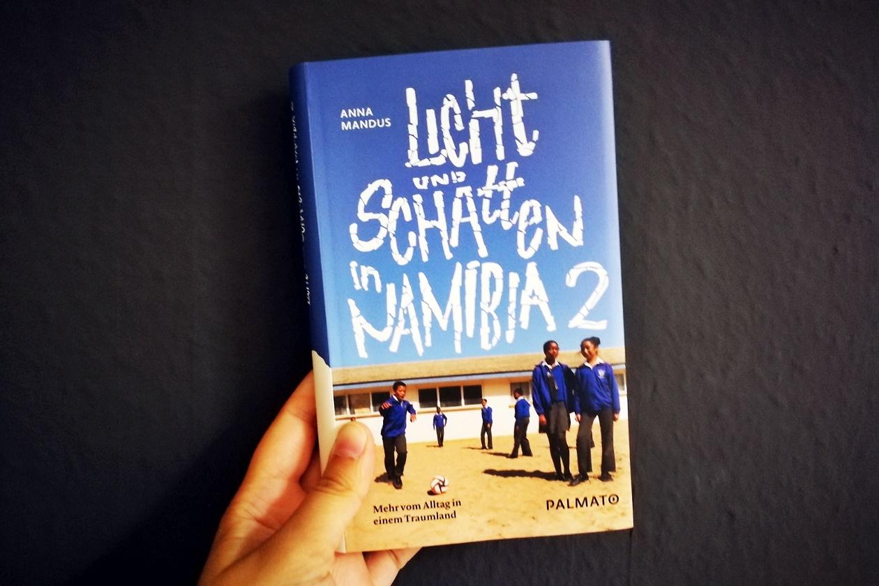 Hand die das Buch Licht und Schatten in Namibia 2 von Anna Mandus hält