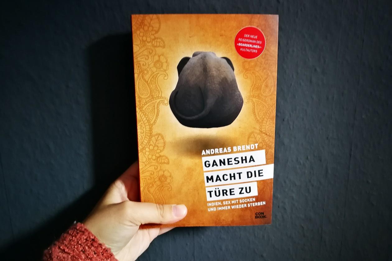 Hand mit dem Buch Ganesha macht die Türe zu