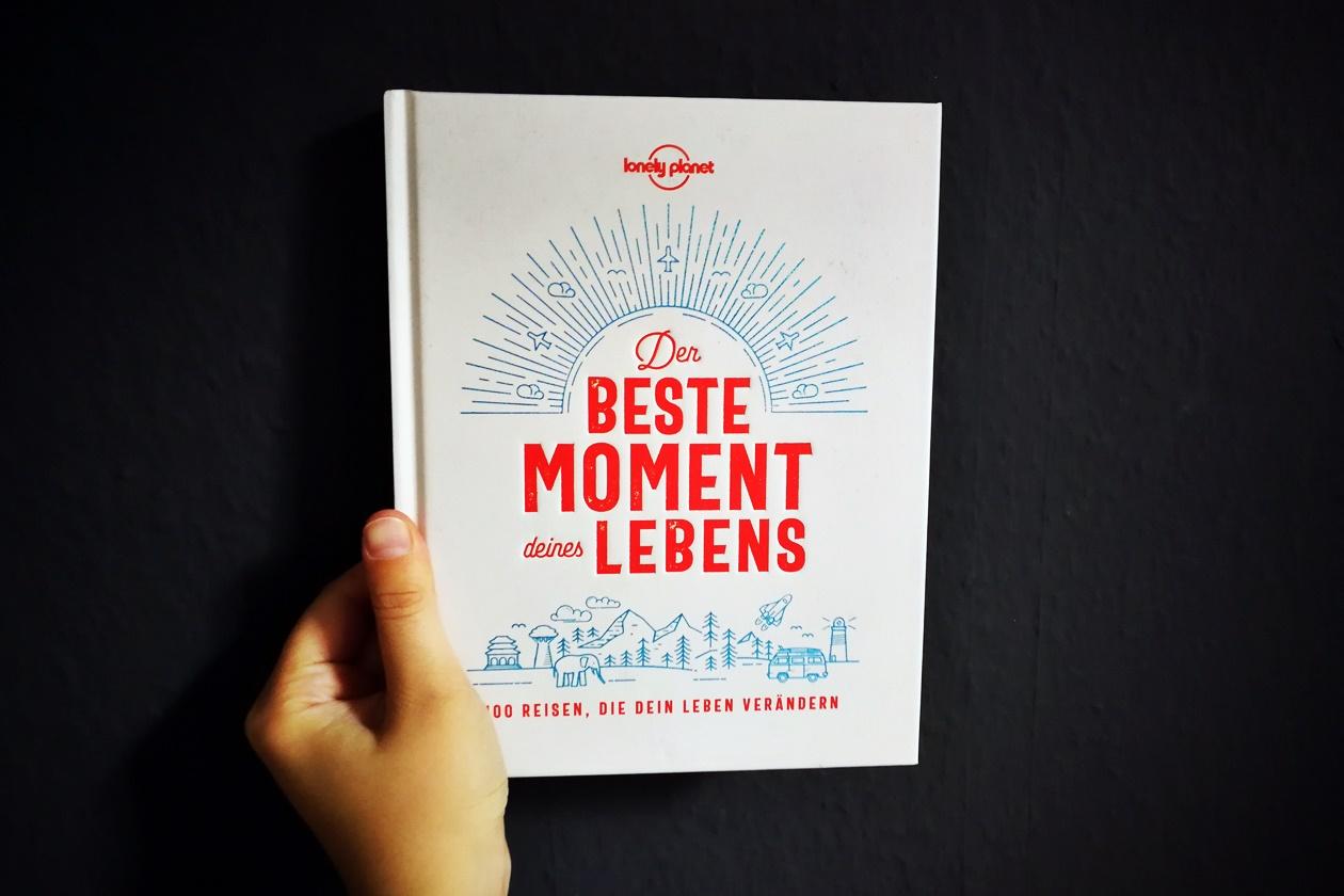 Hand mit dem Buch Der Beste Moment deines Lebens vor grauer Wand
