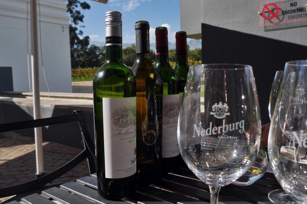 Weinflaschen und Gläser aufgereiht zum Wine Tasting in Nederburg