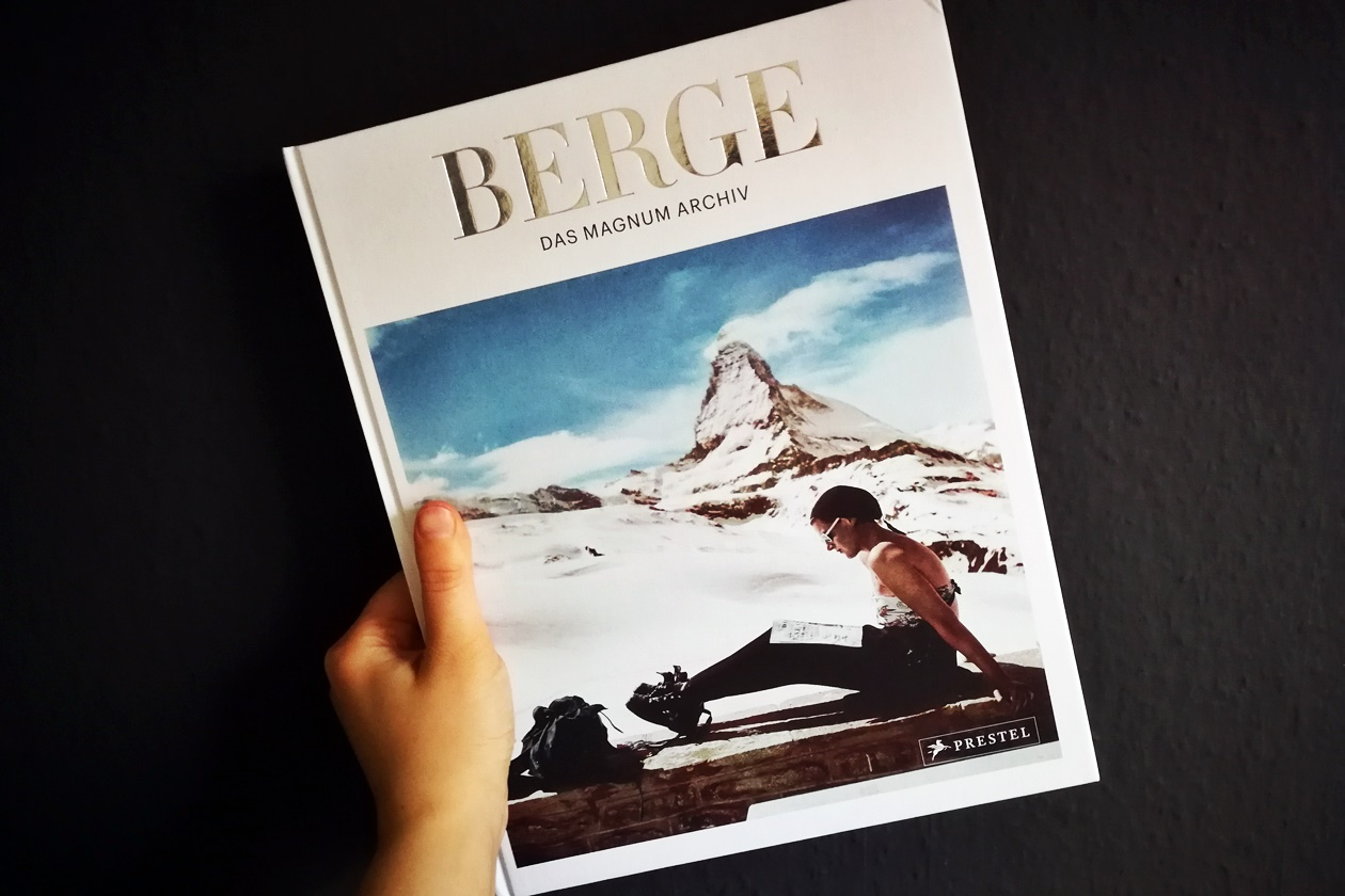 Hand die das Buch Berge - Das Magnum Archiv, hält.