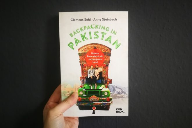 Hand mit dem Buch Backpacking in Pakistan