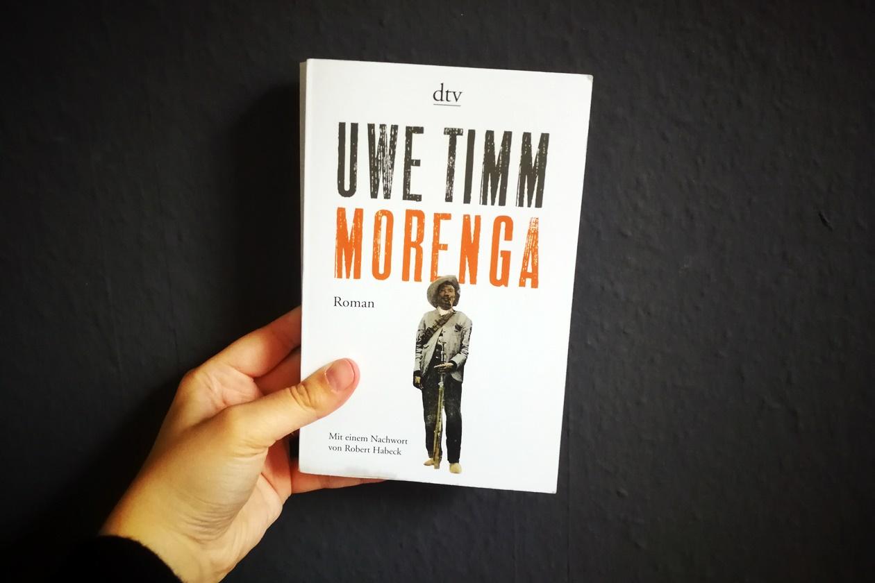 Hand die das Buch Morenga von Uwe Timm hält