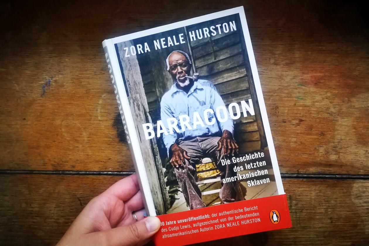 Hand die das Buch Barracoon hält
