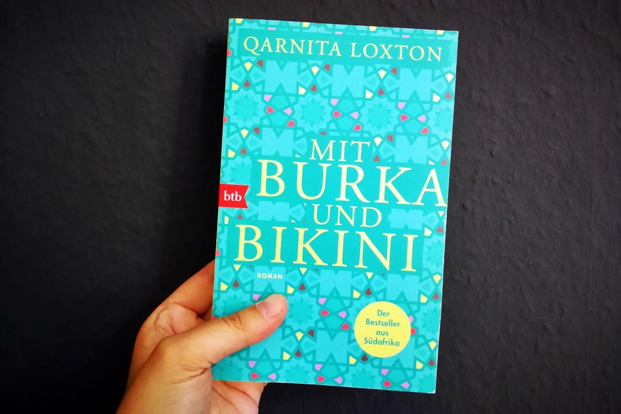 Hand die das Buch Mit Burka und Bikini hält