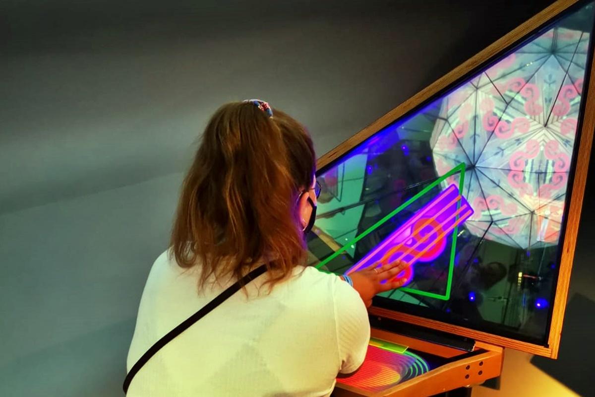 Frau an einem der 350 Experimente die man bei einem Besuch im phaeno Wolfsburg erleben kann