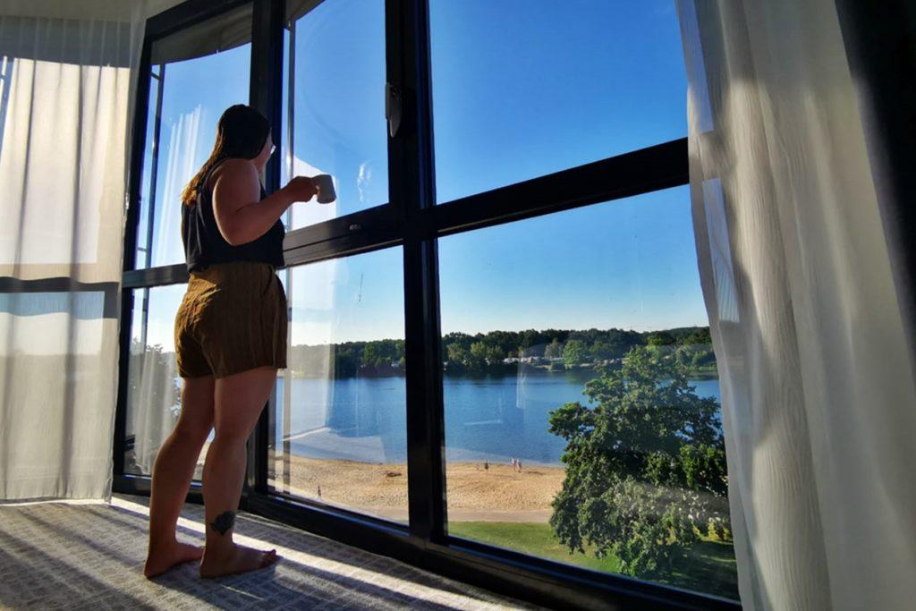Frau steht mit Kaffee an der großen Fensterfront eines Zimmer des Courtyard by Marriott Wolfsburg und schaut auf den Allersee.
