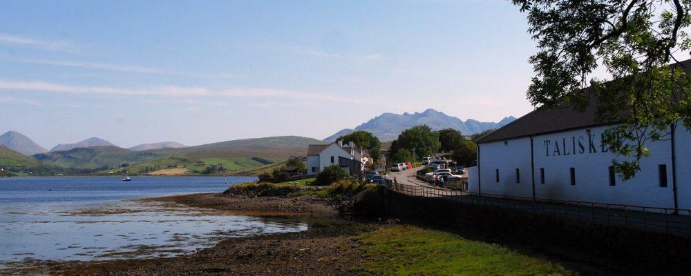 Bucht an der die Talisker Destillery liegt mit großen Bergen im Hintergrund auf der Isle of Skye